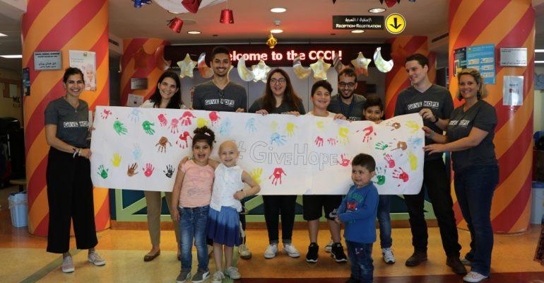 Photo au CCCL avec les bénévoles de SB et les enfants qui ont aidé à faire les dessins